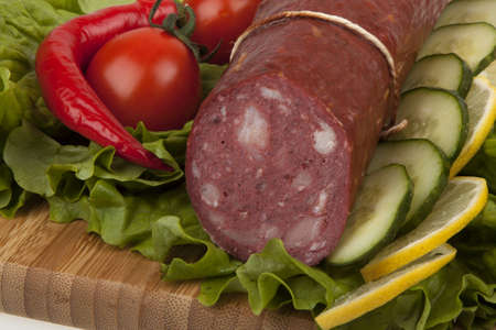 Sausage with vegetables on  kitchen board photo