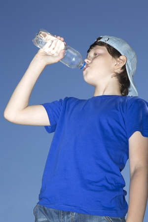 The teenager drinks water from a bottle against the sky photo