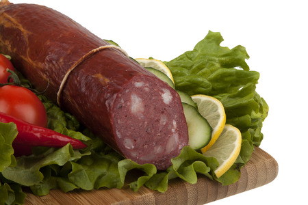 Sausage with vegetables on  kitchen board on white background photo