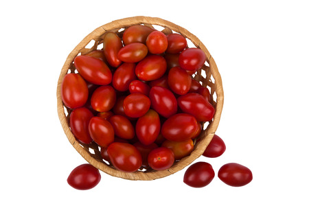 Brown wattled basket with red tomatoes isolated on white background photo