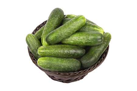 Brown basket with ripe green cucumbers isolated on white background photo