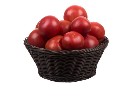 Brown wattled basket with red ripe tomatoes isolated on white background photo