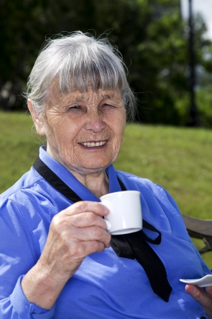 The elderly woman in park on bench with coffee mug in hand photo