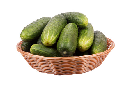 wickerwork: Brown basket with ripe green cucumbers isolated on white background