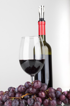spirituous beverages: red wine in glass with grapes isolated on white background