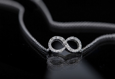 infinity necklace on black background