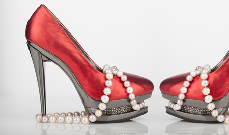 shoe strings: Woman red shoe with pearl necklace on a white background