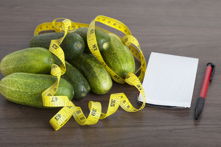 fresh vegetables with a tape measure on a wooden background as a symbol of healthy eating