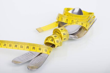top of view of measuring tape near spoon and fork, concept of nutrition and diet on white background with space for text