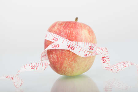 unattached: Red apple and a measuring tape, isolated on white background