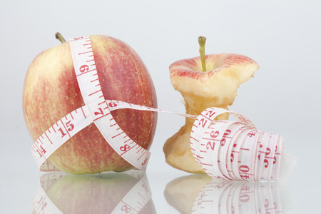 Red apple core and measuring tape. Diet concept