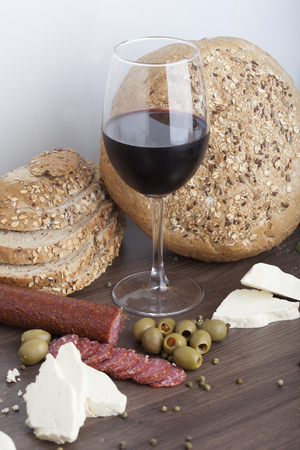Salami sausage on a wooden table with wine and olives Zdjęcie Seryjne
