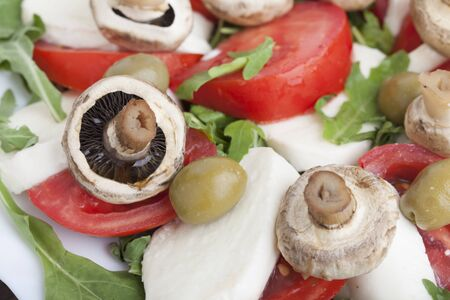 Caprese salad with mozarella cheese, tomatoes , olives and mushrooms