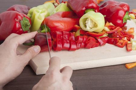 Cook is chopping bell pepper, closeup shoot