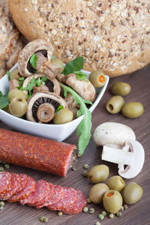 Salami sausage on a wooden table with mushrooms and olives