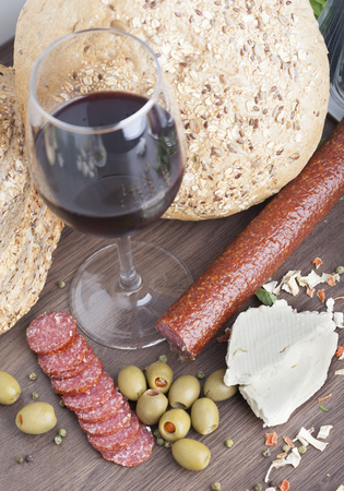 Salami sausage on a wooden table with wine, cheese and olives