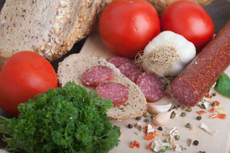 sausage slices, tomato, lettuce, bread on a wooden carving board Zdjęcie Seryjne