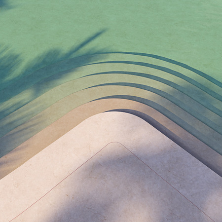 Emerald clear water in a large pool with steps. Swimming pool lit by the morning sun.