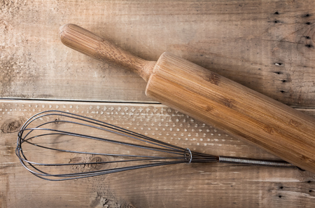 Top view of whisk and rolling pin baking utensils on wooden background Stock Photo