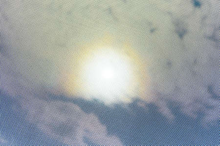 depending: View through a dot mask towards the sky. The strong sunlight causes a halo in the sky. Depending on the zoom level of the photograph the mask may provoke different interferences. Invisible remote wire connections made visible.