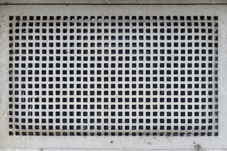 structured: old cellar security grid window with white anti corrosion paint, mildly curved metal of quadrangular pattern form Stock Photo
