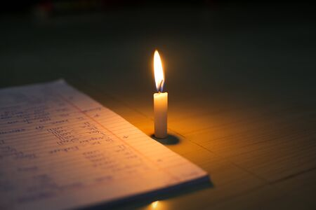 Candle near books. hope for education alive with the light of candle Stock Photo