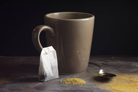 light slate gray: mug and spoon of honey behind raw sugar and tea bag on light gray slate in front of black background