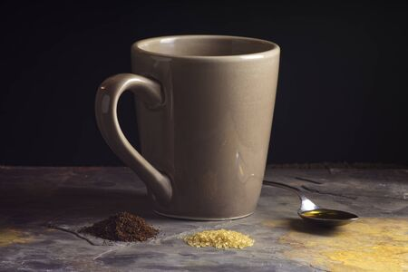 light slate gray: mug and spoon of honey behind raw sugar and coffee grounds on light gray slate in front of black background Stock Photo