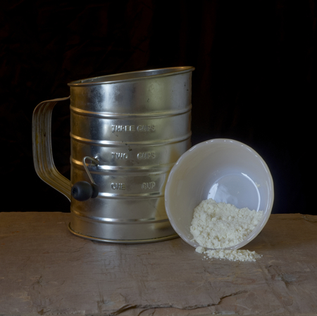 sifter: sifter and small upended bowl spilling flour, on gray slate, in front of black background