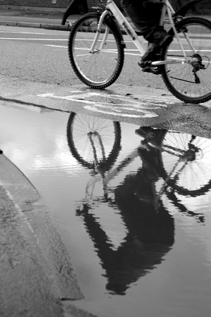 Cyclist on the road reflected in a puddle