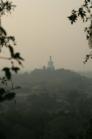 Temple on a wooded hillside seen at dusk through smoggy skies