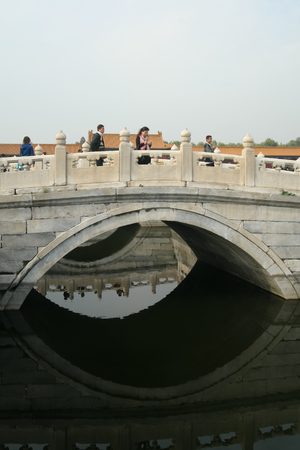 Chinese tourists cross a bridge over water in the Forbidden City, Beijing 報道画像