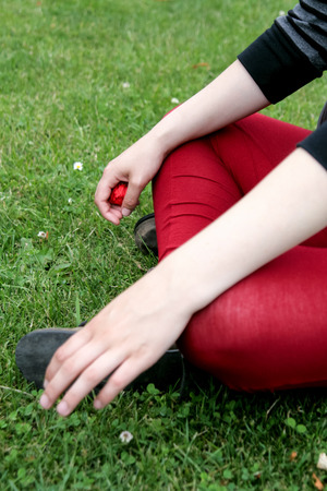Low section of a young caucasian woman wearing red leggings sat on the grass with hands on knees Stock Photo