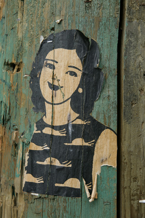 Small paste up drawing of a woman with dark hair, on a green painted lamp post in Vancouver