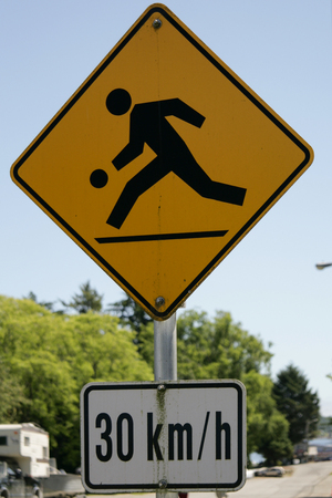 Funny yellow street sign showing children playing at 30 kmph