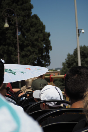 Point of view of tourists on the top desk of a tour bus with ats and umbrellas on a hot day in italy
