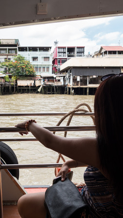 Tourist boat trip on the river in Bangkok, Thailand - a woman resting her hand on the railing Banque d'images - 115706655