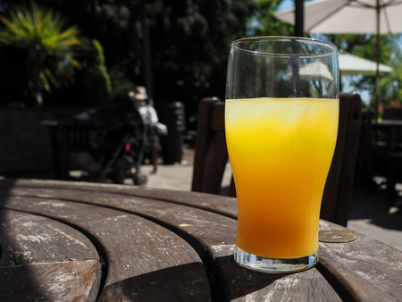 Pint glass full of orange juice on a hot day, on a wooden table with people blurred in the background