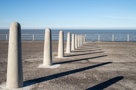 Concrete bollards casting shadows on the promenade by the sea in Margate