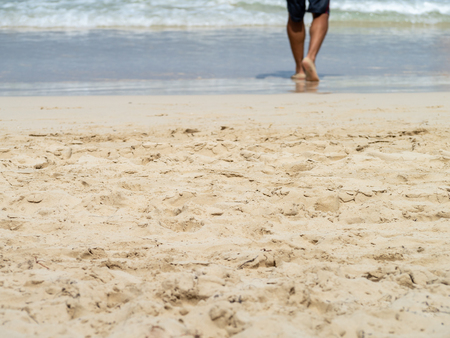 Sunny sandy beach with low section of mans legs walking into the waves