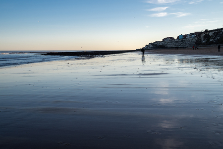 Dusk on the beach at Broadstairs, Kent, with people silhouetted