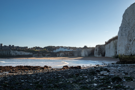 People walking on the beach in the distance at evening in Kingsgate Bay, Broadstairs, Kent