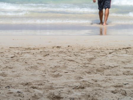 Dreamy low section of barefoot man walking into the waves on a sandy beach