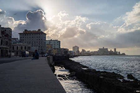 People sitting on the promenade in Havana, Cuba, with sun rays behind the clouds