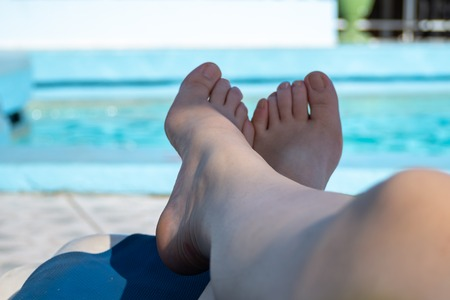 Pair of crossed feet on a sun lounger by a blue hotel swimming pool Stock Photo