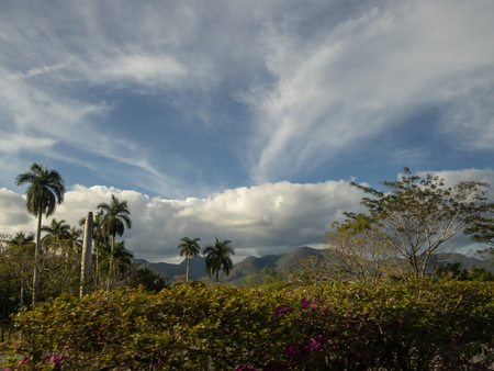 Blue sky and dramatic clouds over the landscape of Cuba with palm trees