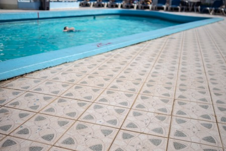 Swimmer in a cool blue pool and a tiled foreground