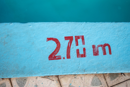 2.70m depth marker painted in red on the side of a blue swimming pool Stock Photo