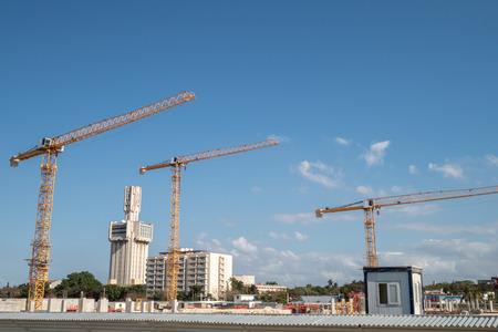 Yellow cranes against a blue sky in Havana, Cuba, on a construction site