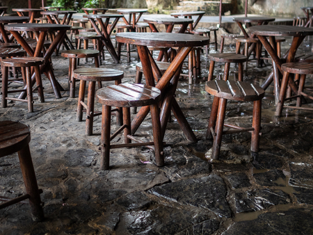 Empty outdoor cafe in cuba, with rustic wooden stools and tables